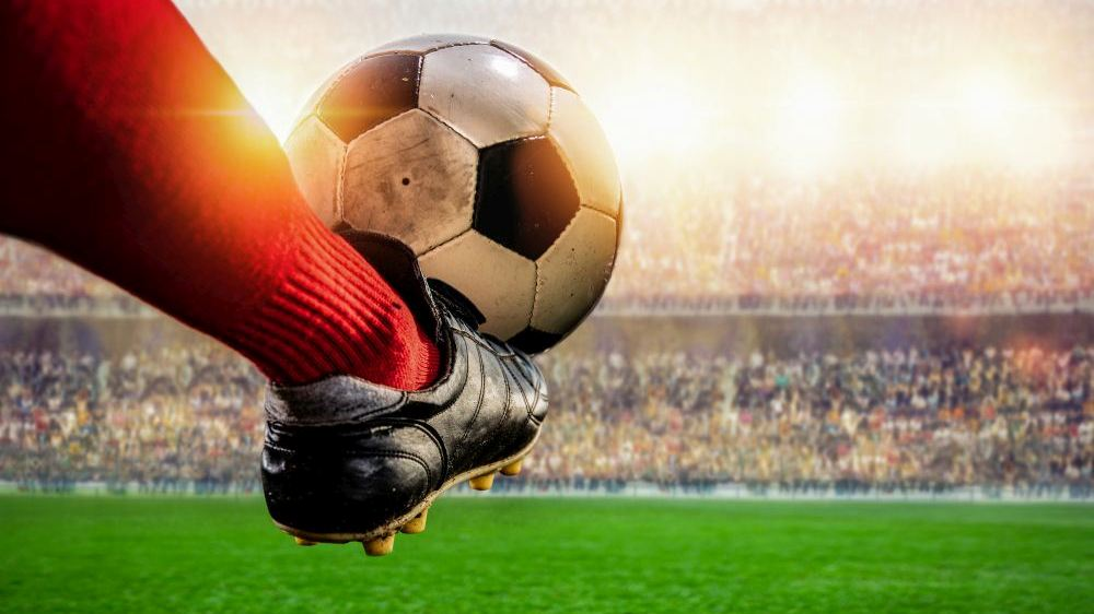 red soccer player kicking ball action in the stadium